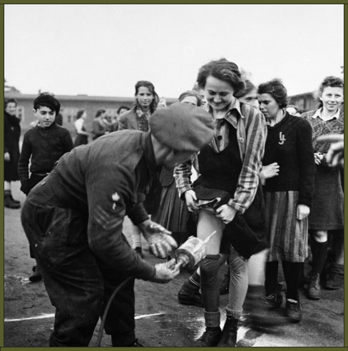 A British doctor administers delousing treatment of DDT up the skirt of an embarrassed-looking female prisoner at Bergen-Belsen, 1945