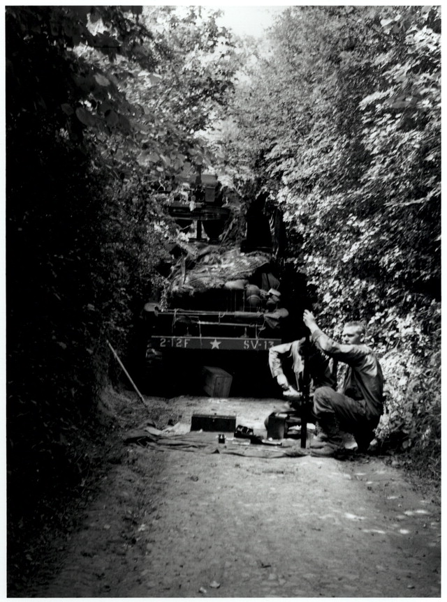 American truck broken down in hedgerow with 2 GIs working on equipment in front of it, Normandy, France.jpg