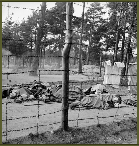 Dying women huddle on the ground behind the barbed-wire enclosure at Bergen-Belsen, 1945