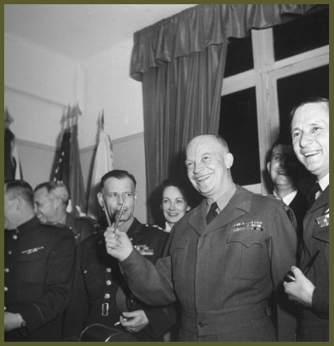 Eisenhower makes V for victory with surrender pens, German and U.S. pen at right, Russian at left