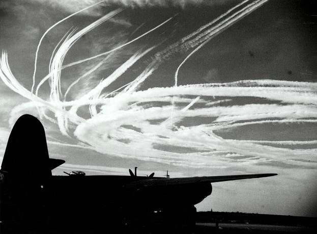 Silhouette of a B-26 with thin vapor trails caused by fighters.jpg