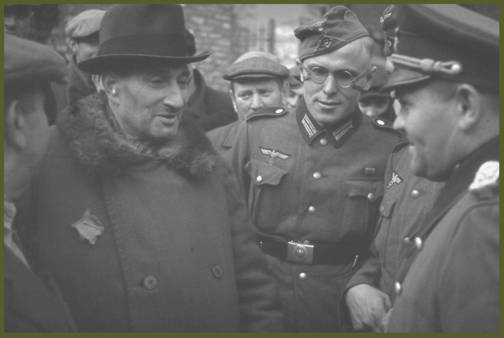 Elderly Jewish man speaks with German officers rounding up Kutno Jews, German-occupied Poland, 1939